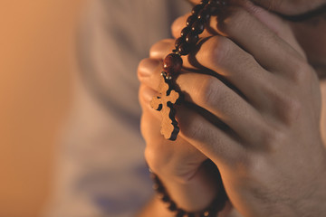 Religious young man with rosary beads, closeup