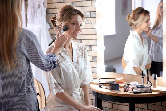 Makeup artist preparing bride before her wedding in room