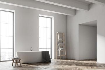 White tub in a white bathroom corner