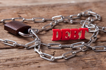 Debt of red letters near the chain with a closed lock on the wood background.