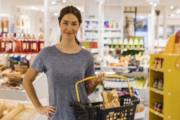 Portrait of smiling casual woman in the market with her basket. Display fruits background. Looking at camera