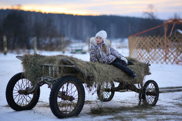 A girl sitting in a cart with hay in a village in the winter evening at sunset