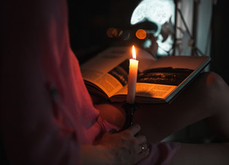 A beautiful young girl in a shirt reading a book at the window-sill by the light of a burning candle at night