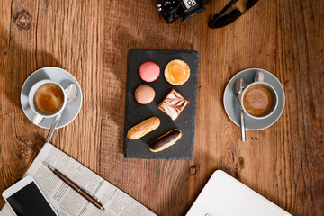 above view still life of two espresso coffee macaroons and french pastries on a rustic wooden tables with a computer, smartphone earphone camera and newspaper