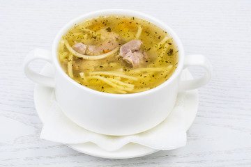 Chicken hot broth with vermicelli in white soup bowl
