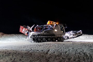 An amazing view of a snowcat in the snow at the top of a ski piste at night in the alps St Moritz Switzerland in winter