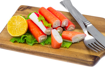 Crab sticks, stuffed with cheese, on wooden board