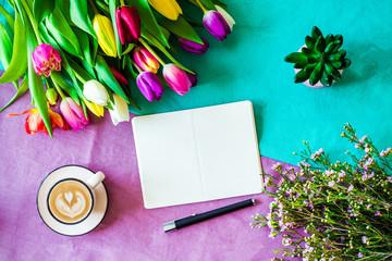 Freifläche auf Notizblock und Stift mit buntem Hintergrund und Tulpen im Frühling von oben zu Ostern