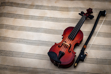 Music and arts concept with a violin on a grunge song sheet with copy space