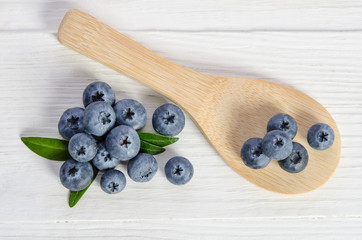 blueberry in wooden spoon and on wooden table