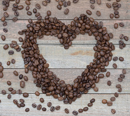 Love Coffee flat lay: an empty heart with coffee beans on a wooden background