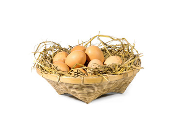 Group of eggs with straw in a bamboo basket isolated on white background.
