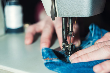 The elderly seamstress is working on sewing machine