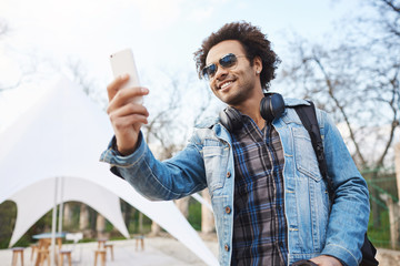 Outdoor shot of attractive young african-american with afro hairstyle and headphones over neck, wearing trendy clothes and glasses, holding smartphone while recording street band in park.