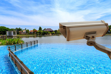 CCTV security camera secure to protect and outdoor swimming pool and lake with beautiful sky. Copy space.
