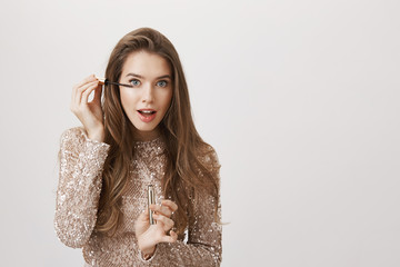 Joyful attractive european female model standing in front of mirror in evening dress and putting on mascara with focused expression and opened mouth over gray background. Girl tries new product