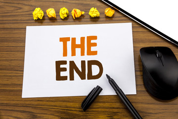 Conceptual hand writing text showing The End. Business concept for End Finish Close written on sticky note paper on the wooden background with marker mouse and tablet office view.