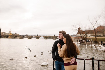 Romantic young couple in Love. Hug on the background of swans in the Vltava River in Prague