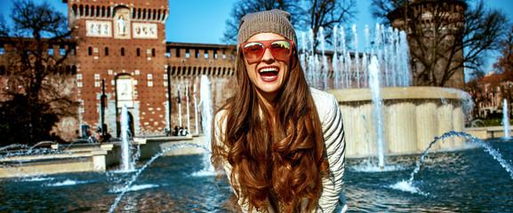 happy modern woman near Sforza Castle in Milan, Italy