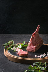 Grilled sliced rack of lamb with yogurt mint sauce served with green salad young beetroot leaves and pink salt on round wooden slate board over dark black table background. Copy space
