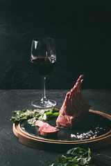 Grilled sliced rack of lamb with yogurt mint sauce served with green salad young beetroot leaves, glass of red wine, pink salt on round wooden slate board over dark table. Copy space. Toned image