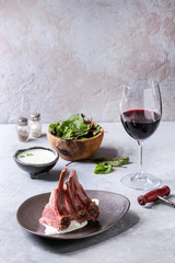 Grilled sliced rack of lamb with yogurt mint sauce served in ceramic plate with green salad young beetroot leaves, glass of red wine over grey texture table.