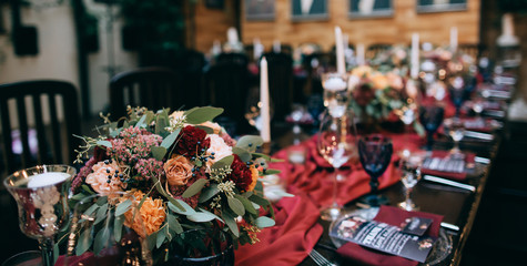 beautiful weding table decoration with red fresh flowers and candles