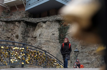 """A woman crosses a foot bridge with attached """"Love Locks"""" at the historical part of Tbilisi"""