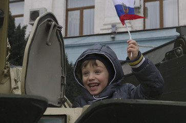 A boy waves a Russian flag as he sits inside an armoured personnel carrier during celebrations of the Defender of the Fatherland Day in Simferopol