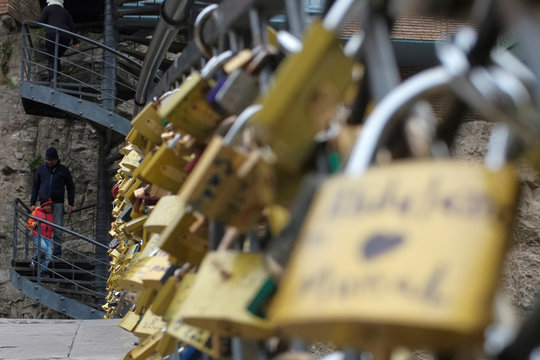 """People walk behind a foot bridge with attached """"Love Locks"""" at the historical part of Tbilisi"""