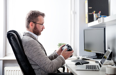 Photographer in home office working with laptop and looking at camera