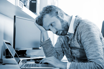Tired man at workplace in office being unhappy