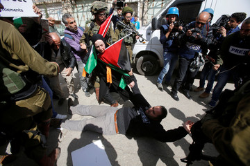 Palestinian demonstrator falls during clashes with Israeli troops at a protest in Hebron, in the occupied West Bank