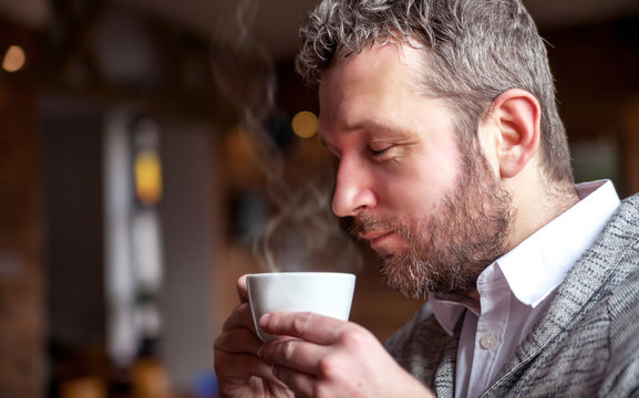 Middle age man smelling aroma of coffee in cafe