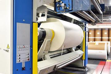 moderne Off-Set-Druckmaschine mit einer Papierrolle in einer Druckerei für Tageszeitungen // Modern off-set printing machine with a paper roll in a print shop for daily newspapers