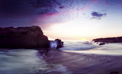 sunset behind cliff,  with purple sky in California