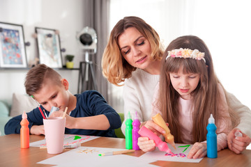 Happy loving family, mother with children together paint at home