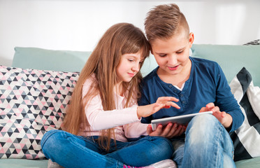 Happy children on sofa at home playing with digital tablet together