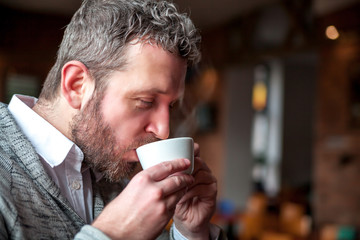 Enjoying man drinking cup of coffee in cafe