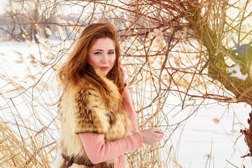 Beautiful young woman in fur vest against the background of a winter landscape