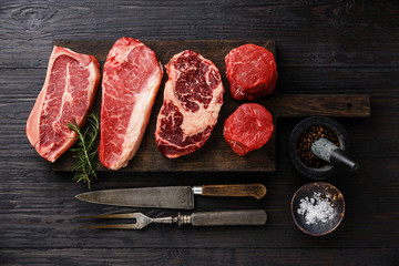 Poster Vlees Variety of Raw Black Angus Prime meat steaks Blade on bone, Striploin, Rib eye, Tenderloin fillet mignon on wooden board