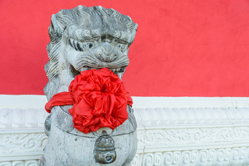 Traditional stone statue of a chinese guardian lion, wearing a big red bow around the neck to celebrate the chinese new year, posted in front of a red wall with a white carved frieze.
