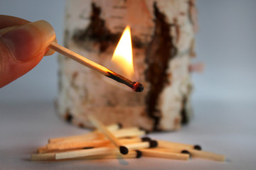 lighted match with a tree log. Don't light a fire in the woods! Concept of environmental destruction. symbol for safety information during a dry heat weather period causing an environmental disaster.