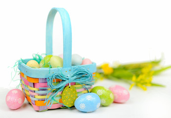 A colorful Easter basket full of sparkly eggs in blue, pink, yellow and green with copy space on a bright white background. Shallow depth of field with yellow flowers in the distance.