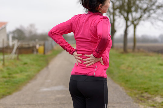 Woman with back or kidney pain clutching her back