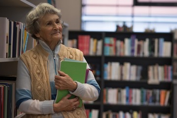 Senior woman holding a book in library