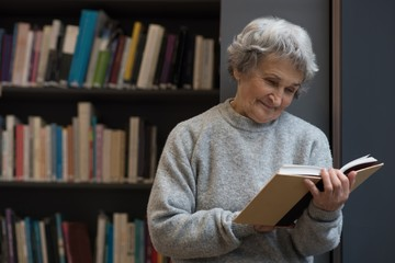 Senior woman reading a book in library