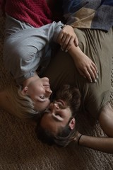 Couple relaxing on floor rug