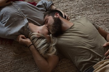 Couple kissing each other while lying in living room