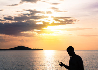 Man holding phone on sunset and sea background